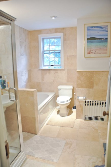 Upstairs bathroom w/jet tub and travertine tiles (we think). Photos is repurposed frame (definitely broke some glass switching out images) with photo from our Honeymoon in St. Thomas (yes, those are my feet).